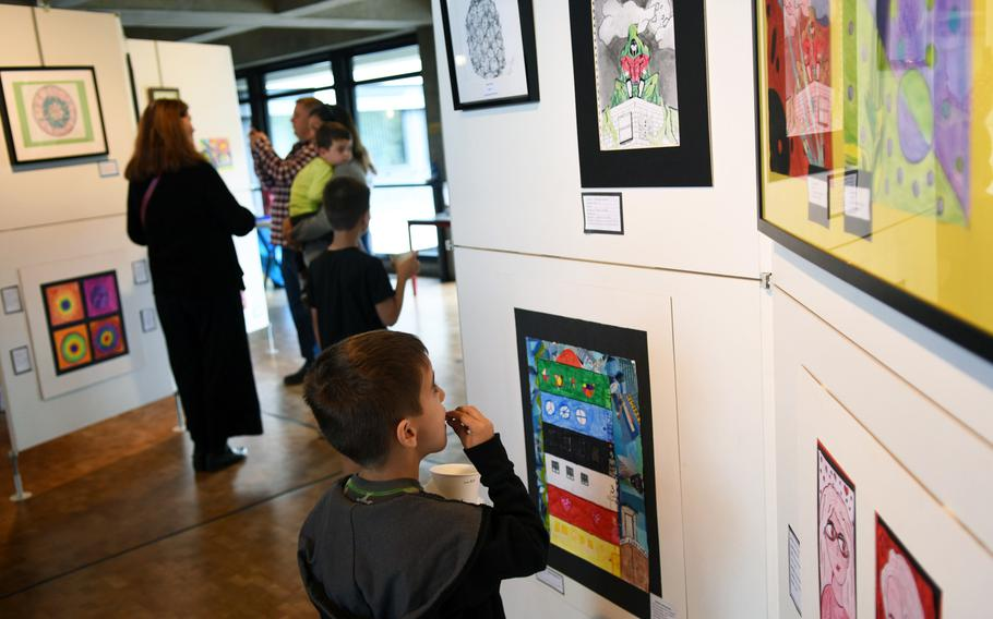 Visitors check out artwork at the opening night of the DODEA art show in Kaiserslautern, Germany, Thursday, May 3, 2018. The exhibit at the city hall runs through the end of May.