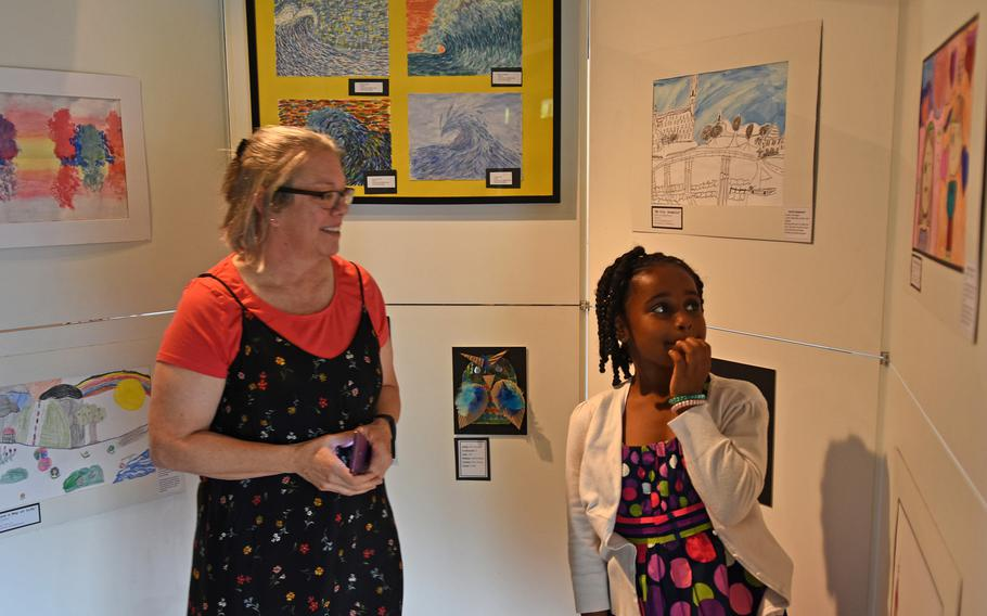 Brooklynn Wilson, a third-grader at Hainerberg Elementary School in Germany, and Jennifer McPhail-Hastings, president of the Overseas Art Education Association, look at Brooklynn's art on Thursday, May 3, 2018, during the opening night of the DODEA art exhibit in Kaiserslautern.