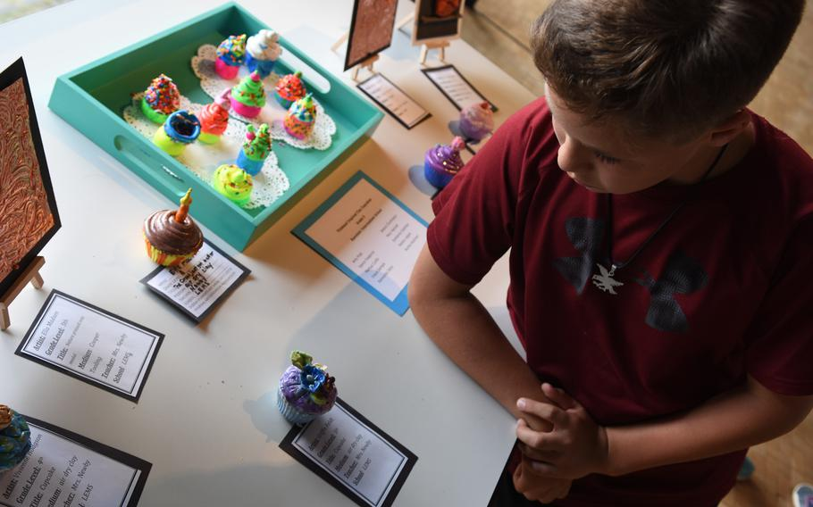 Griffin Feldt, a fifth-grader at Landstuhl Elementary-Middle School in Germany, stands by his cupcake made by air-drying clay. Feldt and other student artists attended the opening night of the annual DODEA art exhibit on Thursday, May 3, 2018, in Kaiserslautern city hall. The show runs through the end of the month.