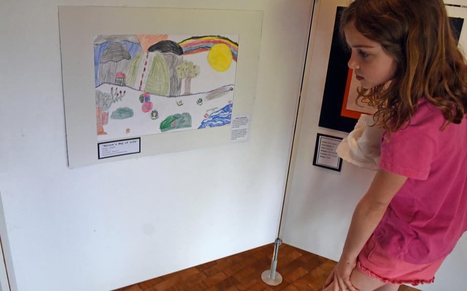 Sara Ligon, a third-grader at Hainerberg Elementary School in Germany, looks at her color pencil artwork on Thursday, May 3, 2018, in Kaiserslautern, Germany. Ligon's work was part of the DODEA art exhibit in city hall, featuring art from six DODEA schools in neighboring communities.