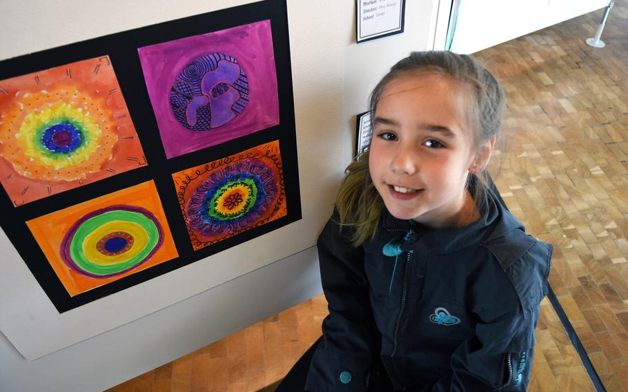 Kayra Russo, a fourth-grader at Landstuhl Elementary-Middle School in Germany, kneels by her artwork called, ''The Dot,'' on Thursday, May 3, 2018, in Kaiserslautern, Germany.