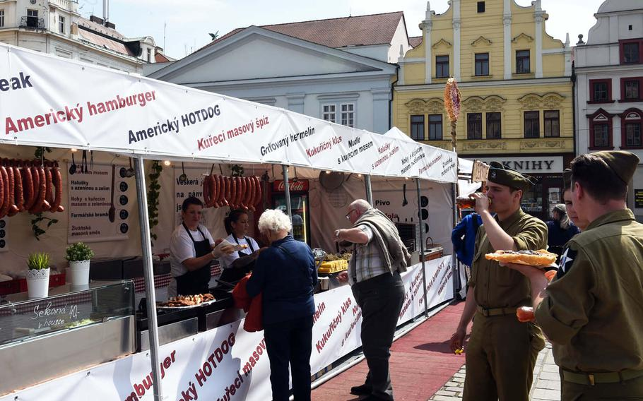 Czech re-enactors, dressed as World War II GIs, enjoy American-style food during the liberation festival in Pilsen, Czech Republic, Friday, May 4, 2018.