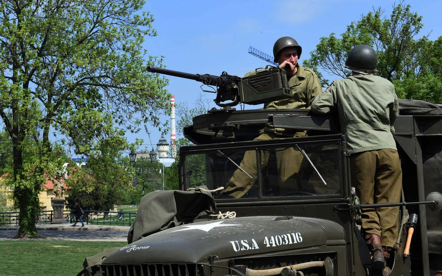 Czech re-enactors, dressed as World War II GIs, talk with each other against the background of the brewery in Pilsen, Czech Republic, Friday, May 4, 2018. The city, which gave the famous beer its name, was commemorating liberation from Nazi occupation.