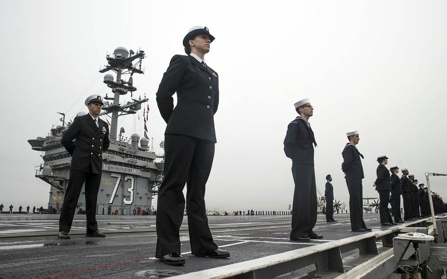 Sailors man the rails on the flight deck of the USS George Washington as the aircraft carrier arrives in its new homeport of Naval Station Norfolk, Va., Dec. 17, 2016.