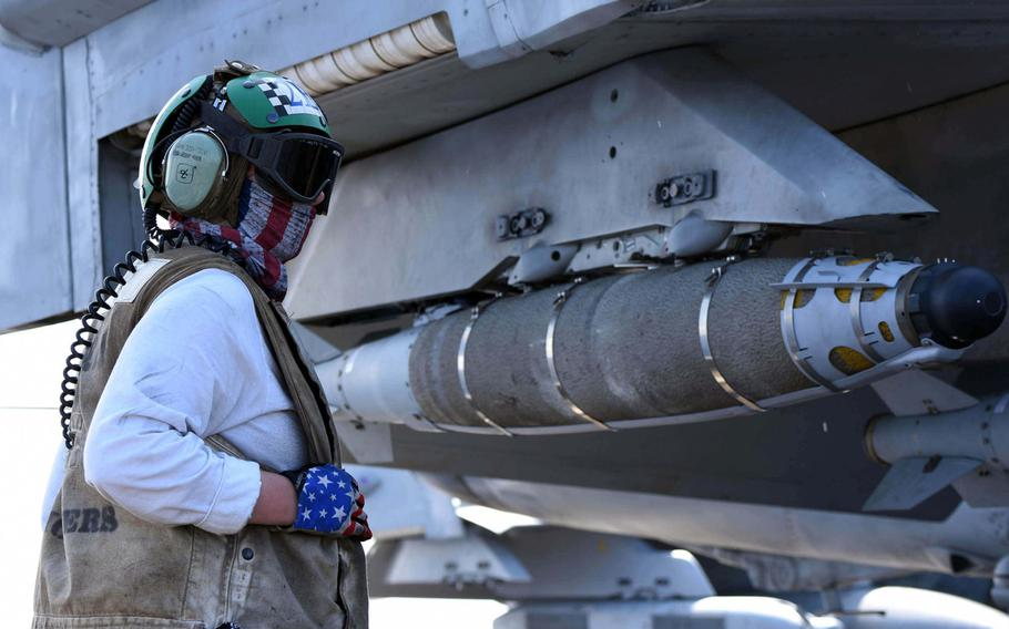 Petty Officer 2nd Class Kelsey Danford assists with moving an F/A-18F Super Hornet on the flight deck aboard the USS Harry S. Truman on May 8, 2018. The Truman Carrier Strike Group is launching airstrikes against ISIS in Syria.