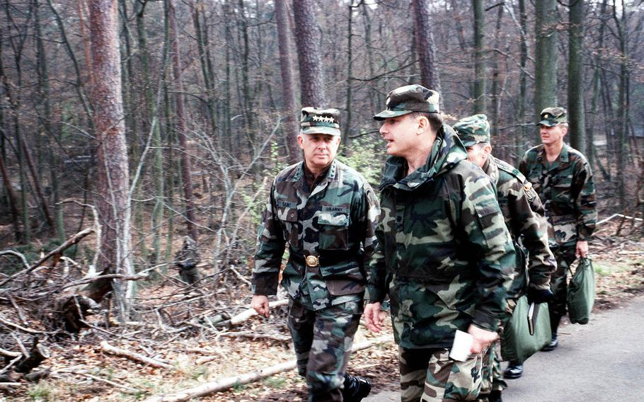 Gen. Crosbie E. Saint, left, former commander of U.S. Army Europe and 7th Army, talks with an officer as he tours the scene of a simulated chemical accident during an exercise in Germany on Aug. 21, 1990. Saint, 81, died on May 7, 2018.