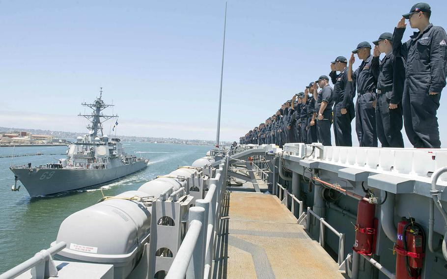 Sailors aboard the USS Essex return salutes to the guided-missile destroyer USS Milius last summer off the coast of Southern California.