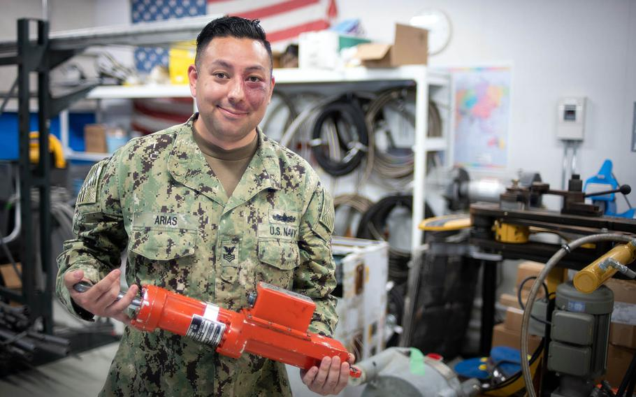 A Naval Beach Unit 7 sailor shows off an actuator used to manipulate hovercraft rudders near Sasebo Naval Base, Japan, May 10, 2018.