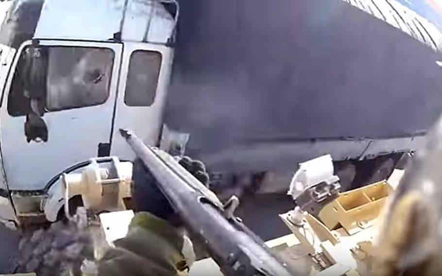 A screengrab of the video that shows a U.S. servicemember firing a shotgun at a truck in Afghanistan. An investigation found that the driver ignored warnings and the servicemember fired a beanbag, in accordance with military rules.