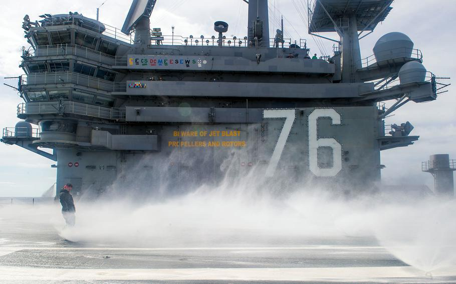Sailors perform a countermeasure washdown on the flight deck of the aircraft carrier USS Ronald Reagan in waters south of Japan, May 12, 2018.