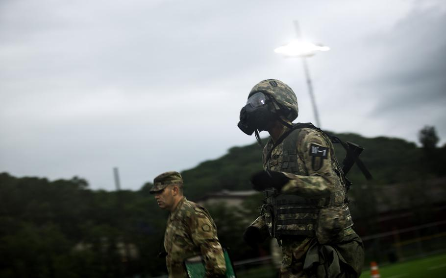 A soldier runs while wearing a gas mask during the Eighth Army Best Warrior competition at Camp Casey, South Korea, Thursday, May 17, 2018.