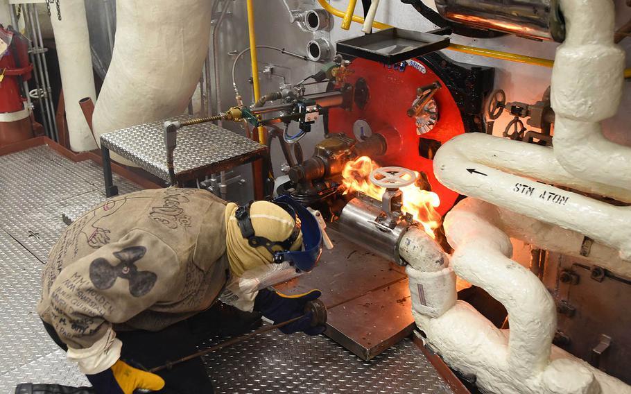 Petty Officer 3rd Class Leonard Barnes lights the One Bravo boiler aboard the USS Blue Ridge at Yokosuka Naval Base, Japan, Tuesday, May 22, 2018.