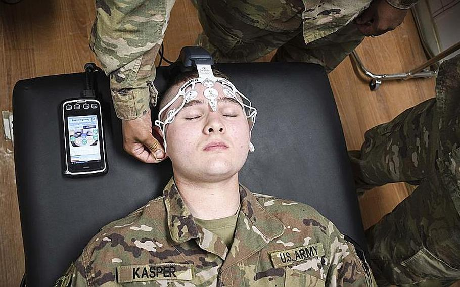 Army Pvt. Jason Kasper, a medic with the 2nd Squadron (Armored), 1st Cavalry, 4th Infantry Division, closes his eyes as another medic places electrodes on his forehead to test for traumatic brain injuries. Soldiers at Advising Post Lightning trained Saturday on the smartphone-sized BrainScope device, a high-tech brain scanner that tests for traumatic brain injuries.