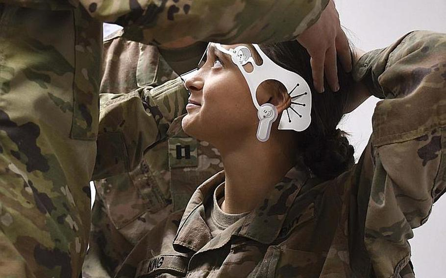 Army Pfc. Shalynn King, a medic with the 2nd Squadron (Armored), 1st Cavalry, 4th Infantry Division, fixes her hair as another medic places electrodes on her forehead to test for traumatic brain injuries. Soldiers at Advising Post Lightning trained Saturday on the smartphone-sized BrainScope device, a high-tech brain scanner that tests for traumatic brain injuries.