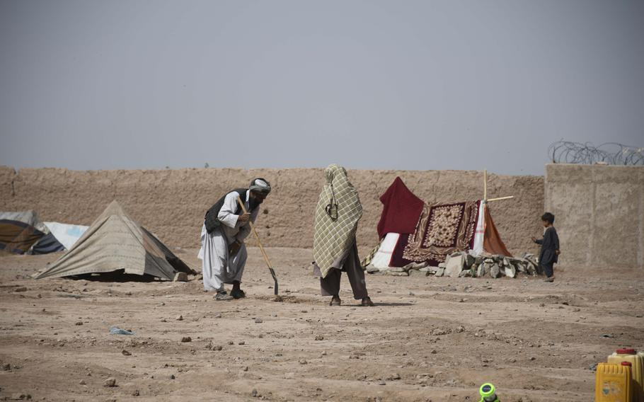 An Afghan man prepares his tent site June 2, 2018, in a camp for internally displaced people on the outskirts of Herat.