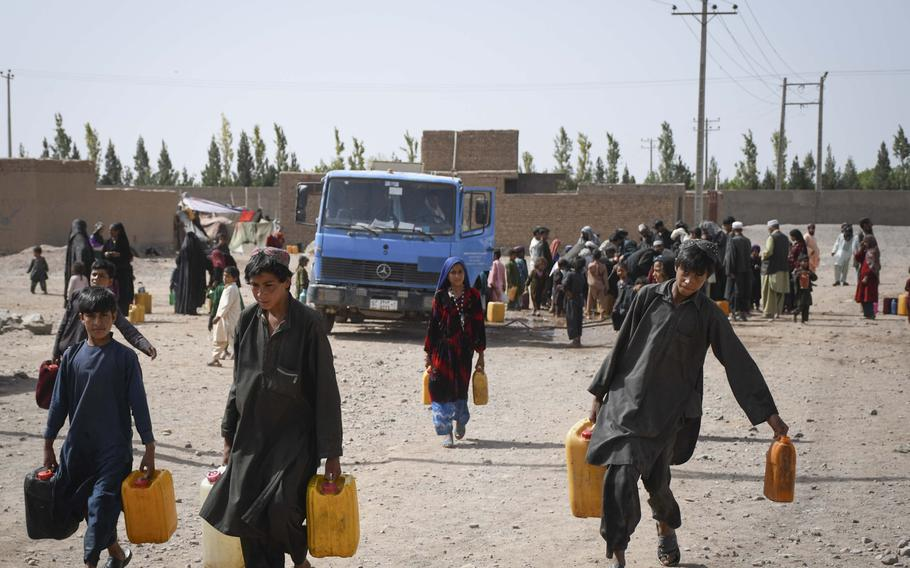 Afghan children draw water delivered by the city of Herat to the estimated 20,000 internally displaced people who have settled into camps on the outskirts of Herat due to drought and warfare.