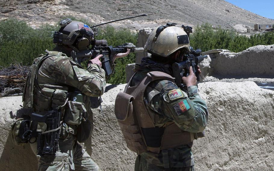 An Afghan commando and a U.S. Special Forces soldier scan the horizon for enemy movement during an operation to find Taliban leadership in Wardak province, May 24, 2018.