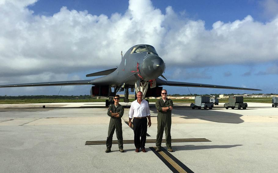 Riki Ellison poses with airmen and a B-1 Lancer stealth bomber at Andersen Air Force Base, Guam, in December 2017.
