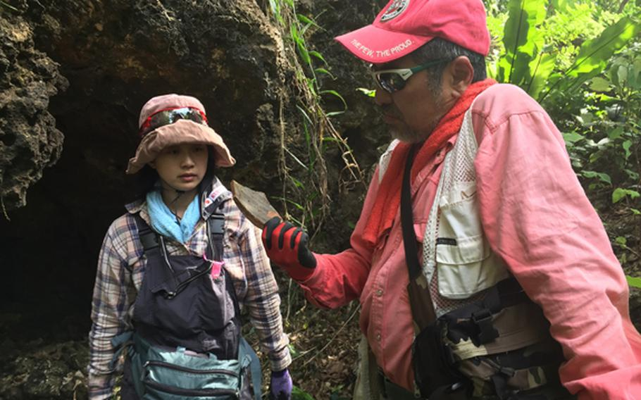 Kuentai-USA secretary general Yukari Akatsuka, left, and founder Usan Kurata, study pottery fragments found in former Japanese fighting positions during the Battle of Okinawa in the Okinawan jungle May 9, 2018, while looking for the remains of a missing U.S. Marine.