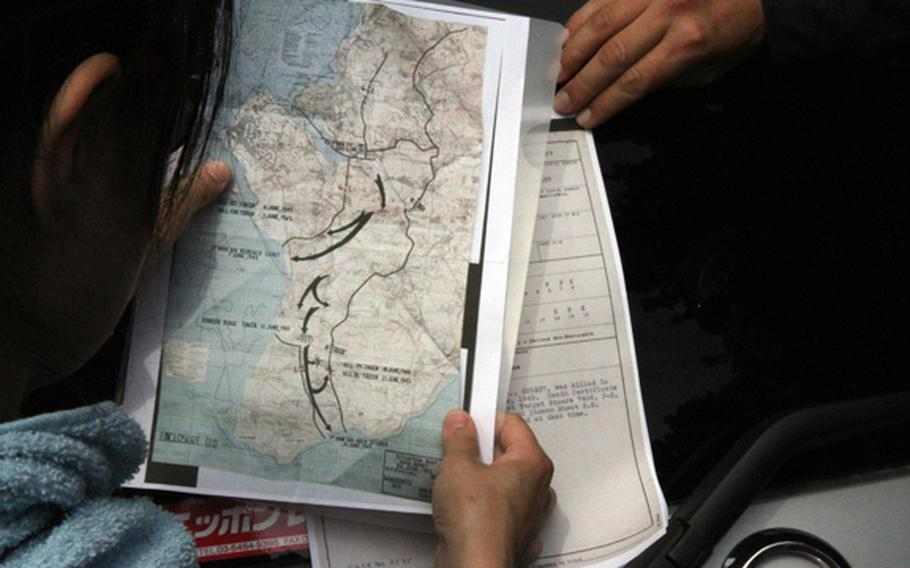 Kuentai-USA secretary general Yukari Akatsuka studies U.S. military maps and personnel files on missing servicemembers from World War II before taking to the Okinawa jungle May 9, 2018, in an attempt to find a missing U.S. Marine lost during the Battle of Okinawa.