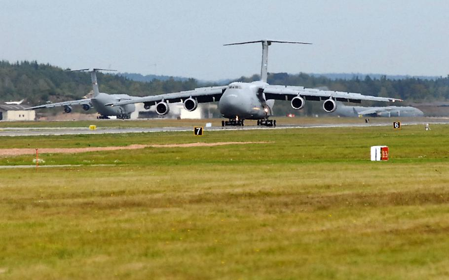 A C-5 Galaxy rolls down the Ramstein Air Base, Germany, runway, as a C-17 Globemaster III, right, and another C-5 wait to take off.  The U.S. is said to be considering a large reduction of troops in Germany, which could involve sending many troops back to the U.S.