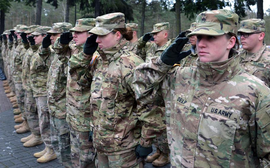 American soldiers salute during the playing of the national anthem during a welcoming ceremony for them at a base in Zagan, Poland, in January 2017. The U.S. is said to be considering a large force reduction in Germany, which could involve sending many troops back to the U.S. and perhaps sending some to Poland.
