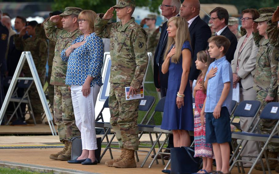 Soldiers and civilians stand during the playing of the American national anthem at the U.S. Army Garrison Rheinland-Pfalz change-of-command ceremony in Kaiserslautern, Germany, Wednesday, July 11, 2018.
