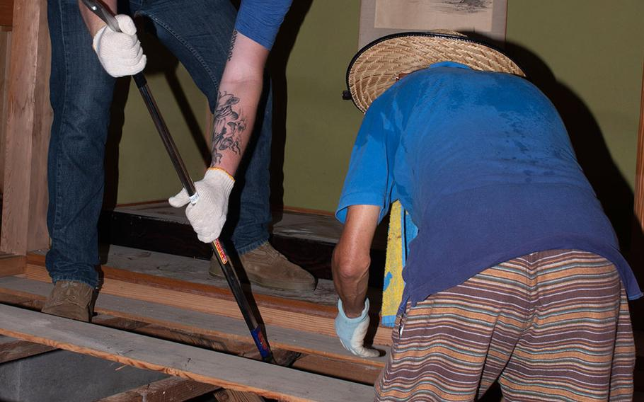 Navy Seaman Kyle Tatro, a corpsman assigned to Marine Air Group 12, helps remove floor boards from a house in the Shuto area of Iwakuni, Japan, on July 12, 2018.