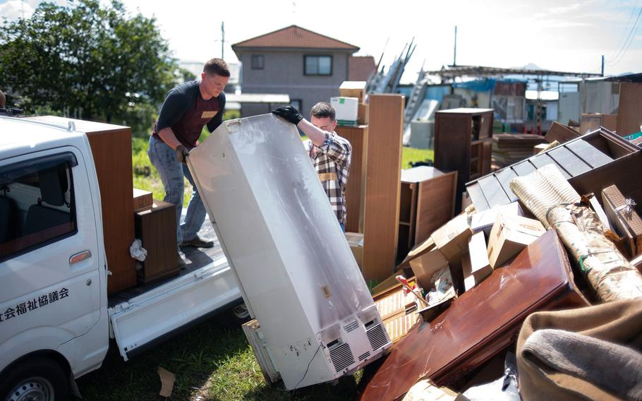 Two Marines assigned to Marine Corps Air Station Iwakuni unload a refrigerator that was destroyed by recent flooding in the Shuto area of Iwakuni, Japan, on July 12, 2018.