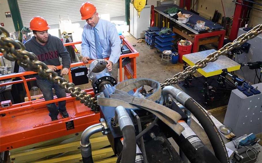 Richard Christenson, right, a civil and environmental engineering professor, and Michael Harris, a doctoral student attach a mounting ring to a hydraulic water pump at a University of Connecticut laboratory.