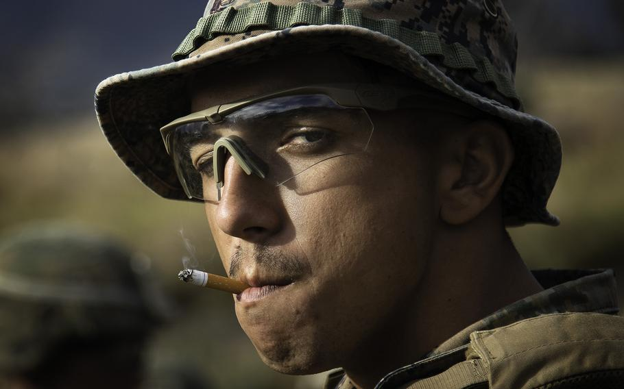 A Marine takes the last drag of his cigarette before conducting a live fire drill at Pohakuloa Training Area, Hawaii, Friday, July 13, 2018.