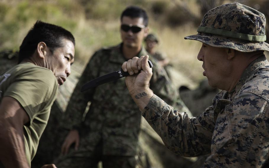 1st Sgt. William Radebaugh, Company B, 1st Battalion, 3rd Marines lunges at his Japanese counterpart with a rubber knife at Pohakuloa Training Area, Hawaii, Friday, July 13, 2018.