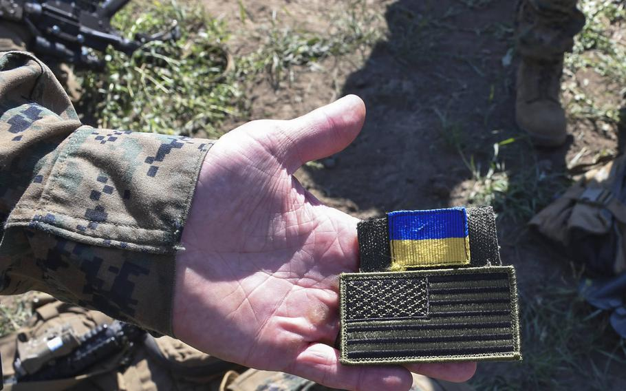 Sgt. Chad Sparks of Hanover, Penn., is pictured here at an assembly area where U.S. and Ukrainian marines were set to mount a company attack on Saturday, July 14, 2018, displaying a Ukrainian flag patch that he traded with one of his Ukrainian naval infantry counterparts for during the large-scale Exercise Sea Breeze. Sparks said he might trade the U.S. flag patch for another souvenir of the training exercise.