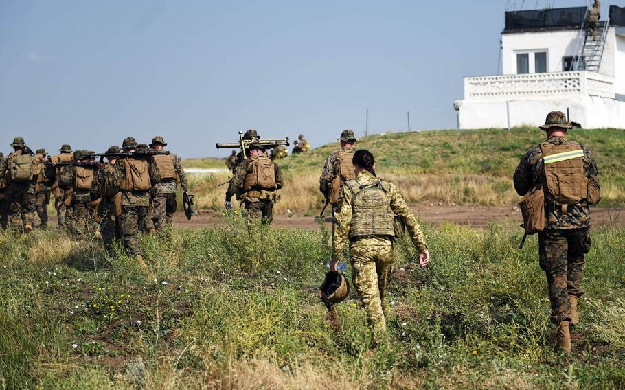 A Ukrainian translator walks with a group of U.S. Marines during the Sea Breeze exercise near Mykolaiv, Ukraine, Thursday, July 12, 2018.