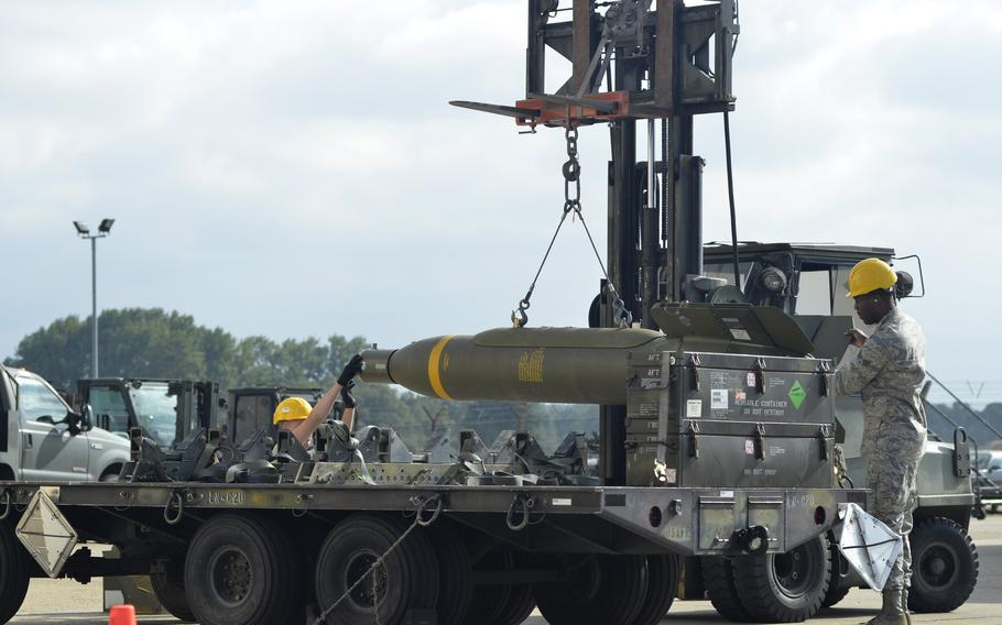 Airmen carefully load a 5,000-pound conventional bunker buster onto a trailer during a combat ammunition production exercise at RAF Lakenheath, England, Tuesday, July 17, 2018.