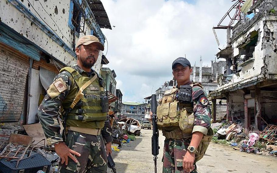 Philippine Rangers Capt. Alex Estabaya and Capt. Ramse Dugan, who fought in the battle to liberate Marawi from Islamic State insurgents, stand in Marawi City, Philippines, in November.