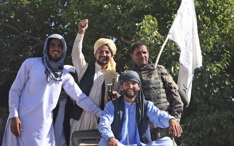 Residents of a Taliban district and an Afghan army soldier pose for photos with a Taliban flag in Logar province, June 16, 2018. Across the country, photos of Taliban and government troops taking photos of each other spread online during an unprecedented cease-fire between the Taliban and the Afghan government.