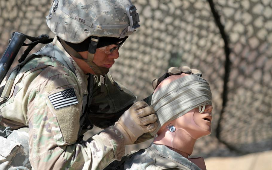 Pfc. Kyle Ishikawa, infantryman, Company A, 2nd Battalion, 23rd Infantry Regiment, 1st Stryker Brigade Combat Team, 4th Infantry Division, practices first aid on an open head wound during Expert Infantryman Badge evaluations on March 15, 2016. The Army is planning to revamp evaluations for the badge.
