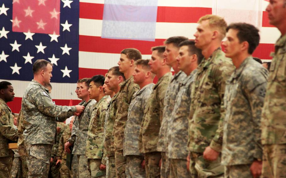 """Col. Curtis D. Taylor, commander, 1st Stryker Brigade Combat Team, 4th Infantry Division, awards 33 """"True Blue"""" soldiers with an Army Commendation Medal during an Expert Infantryman Badge ceremony on March 18, 2016. The Army is planning to revamp evaluations for the badge."""