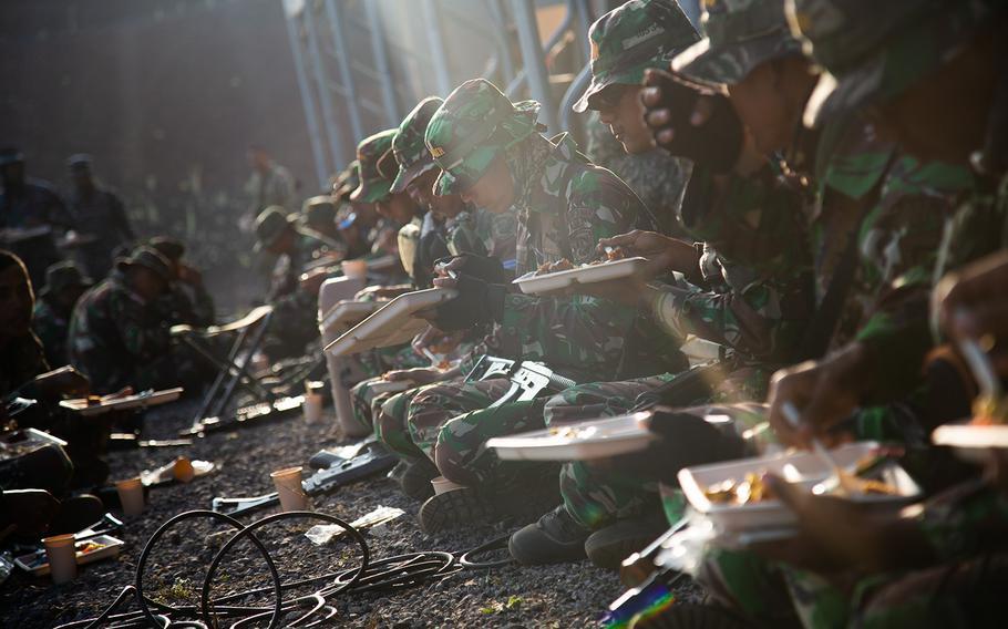 Indonesian marines enjoy hot chow during Rim of Pacific drills at Pohakuloa Training Area, Hawaii, Sunday, July 15, 2018.