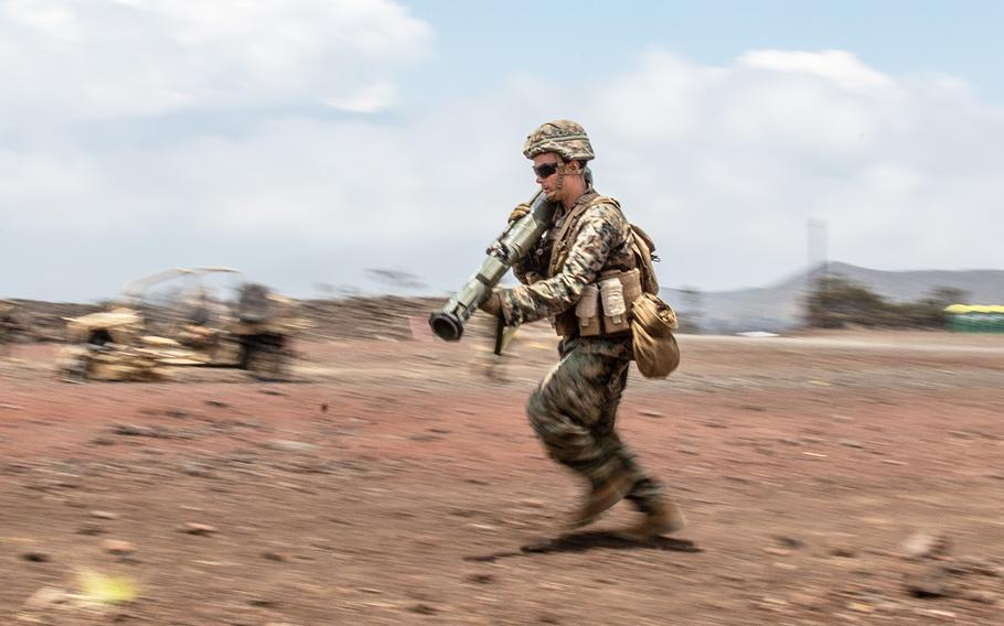 A U.S. Marine rushes down a range with a simulated AT-4 anti-tank rocket launcher during the Rim of the Pacific exercise at Pohakuloa Training Area, Hawaii, Wednesday, July 18, 2018.