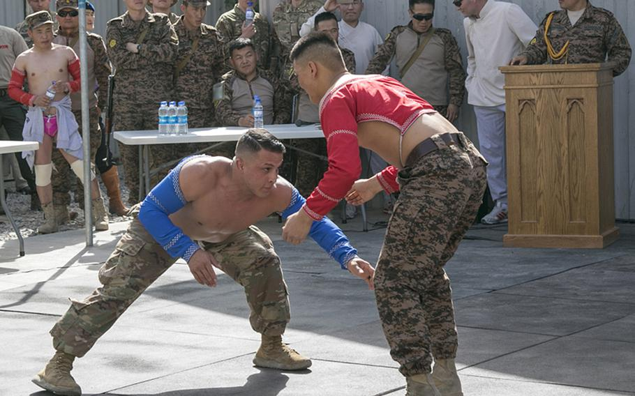 Spc. Michael Pereyra, left, 24, of the 1st Squadron, 180th Cavalry Regiment from Oklahoma City, Okla., faces off against an opponent in Mongolian-style wrestling at New Kabul Compound in Kabul, Afghanistan, July 12, 2018, as part of a festival celebrating the Mongolian revolution.