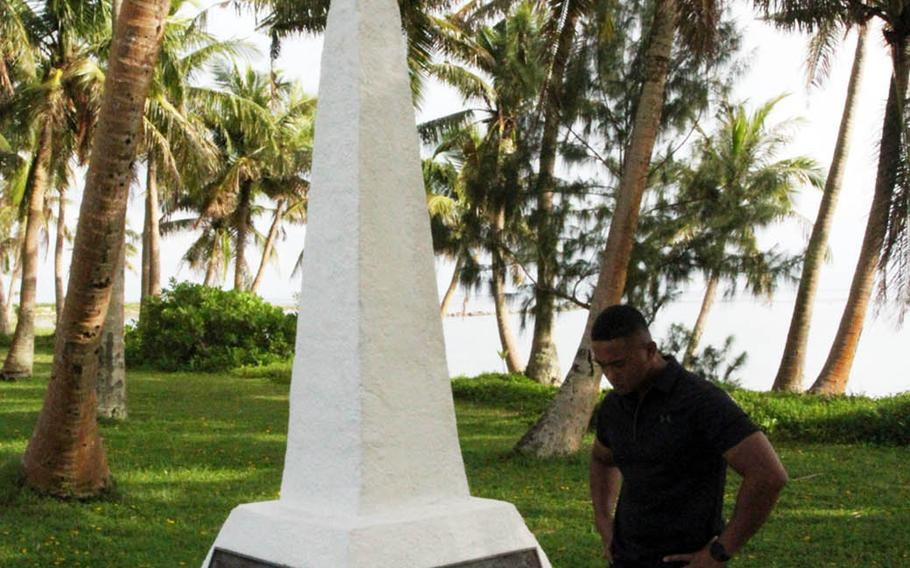 A member of the Okinawa-based 3rd Marine Division reflects at a monument near Asan Beach, Guam, dedicated to the Marine liberators, Wednesday, July 18, 2018.