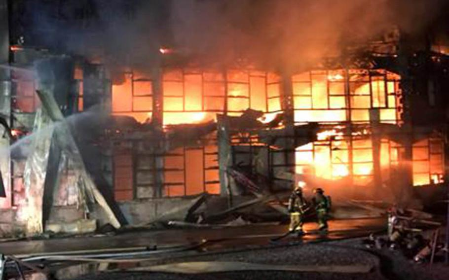 Emergency personnel from Yokosuka Naval Base, Japan, help fight a fire at an off-base warehouse, Sunday, July 22, 2018.