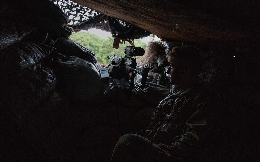 An opposing forces soldier mans a fighting position during the Lightning Forge exercise at Kahuku Training Area, Hawaii, Sunday, July 22, 2018.