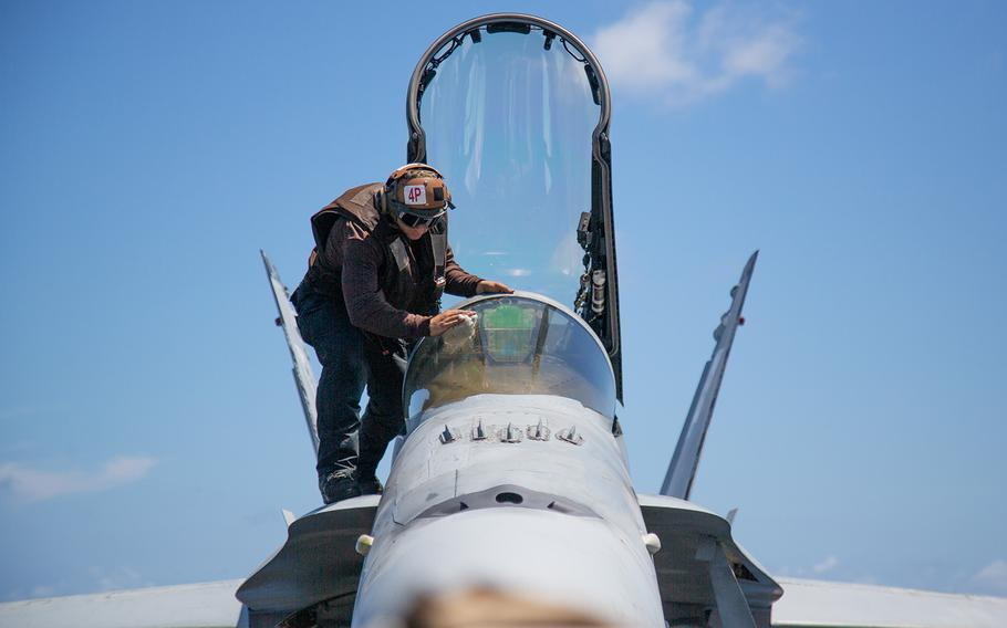 A sailor cleans the cockpit of a jet on the USS Carl Vinson off the coast of the Hawaiian islands, Saturday, July 21, 2018.