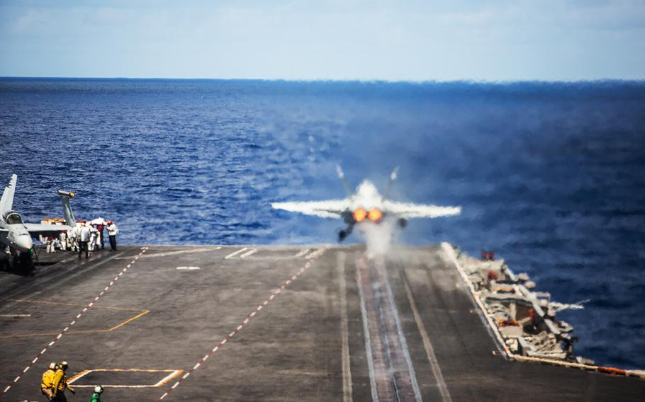An F/A-18C Hornet from Strike Fighter Squadron 34 takes off from the USS Carl Vinson off the coast of the Hawaiian islands, Saturday, July 21, 2018.