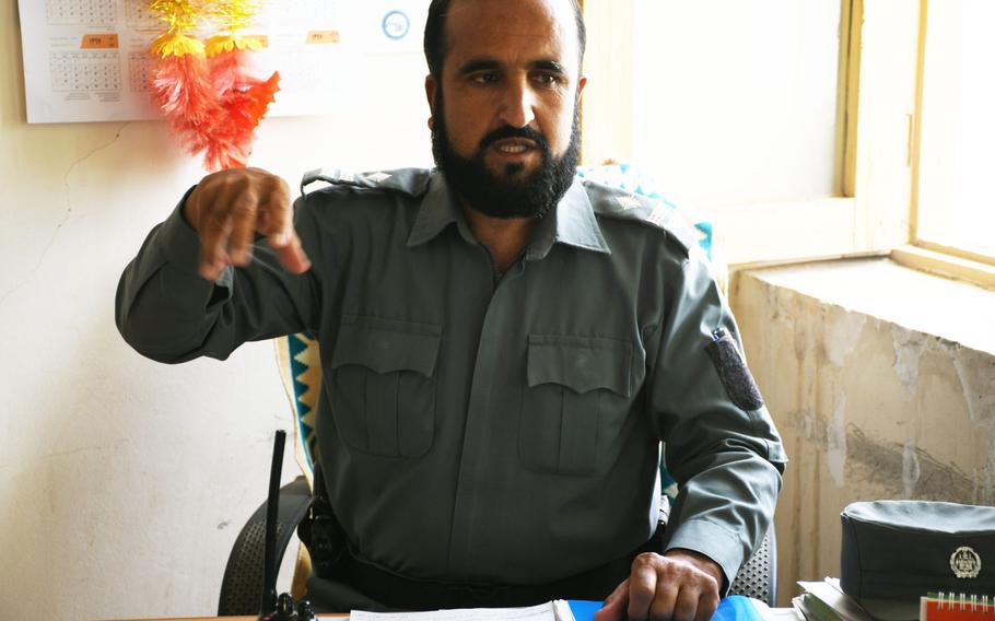 Noor Rahman Haqpal, the deputy police commander for Khak-e-Jabar district in Kabul province sits at his desk on Wednesday, July 18, 2018, explains how the Taliban's presence in the district has grown since a cease-fire last month.