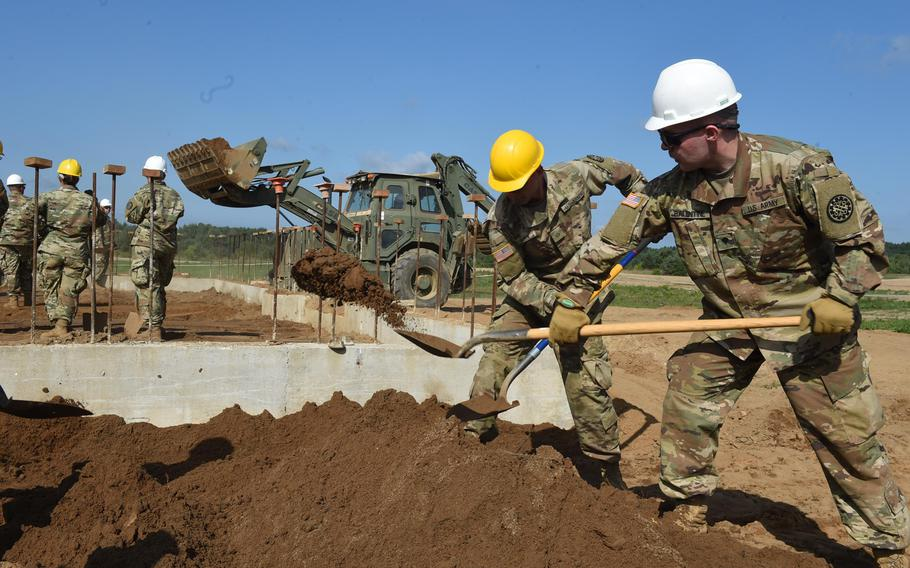 Pfc. Anthony Sevela, left, and Spc. Devan Balentine shovel dirt around new facilities being built at Drawsko Pamorskie Training Area, in Poland, Tuesday, July 25, 2018.