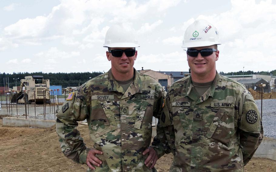 Sgt. 1st Class Andrew Sovey, left, and his brother, Staff Sgt. Stephen Sovey, engineers from Michigan's Upper Peninsula, in front of one of their work sites at Drawsko Pomorskie, Poland, where they are constructing tank range facilities, Wednesday, July 26, 2018.